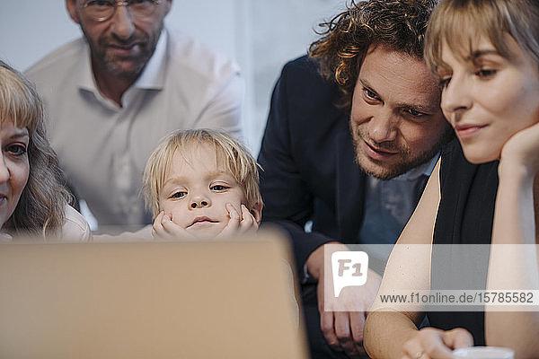 Geschäftsteam mit einem Jungen  der im Büro auf einen Laptop schaut