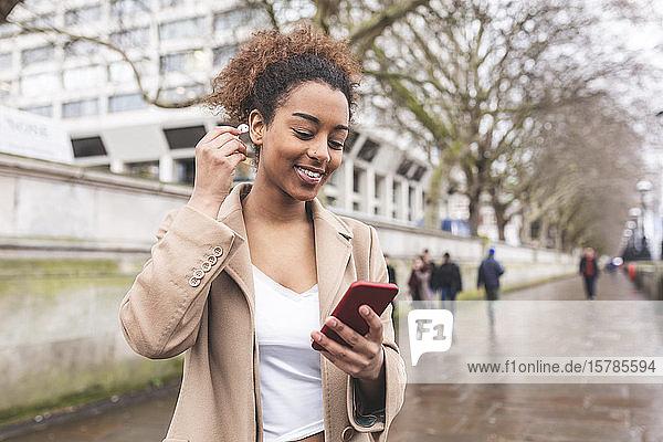 Lächelnde junge Frau mit Handy und Ohrstöpseln in der Stadt  London  Großbritannien