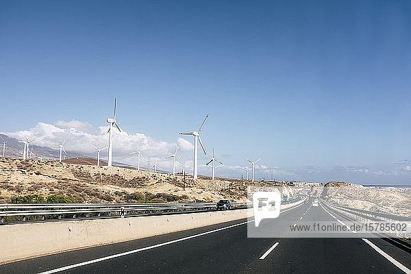Himmel über gerader Autobahn  die sich entlang des Windparks erstreckt