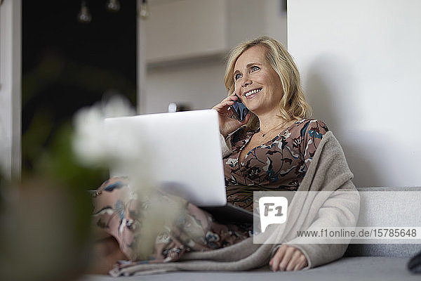 Blond woman with smartphone and laptop on couch at home