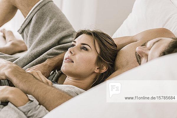 Liebevolles junges Paar im Bett liegend