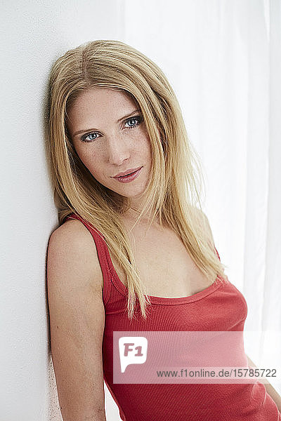 Portrait of beautiful blond young woman wearing red top