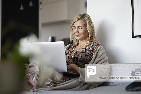 Blond woman using laptop on couch at home