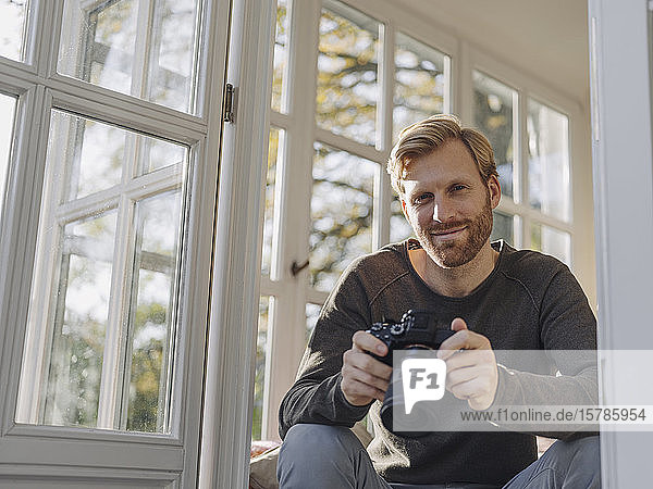 Portrait of man holding camera in sunroom at home