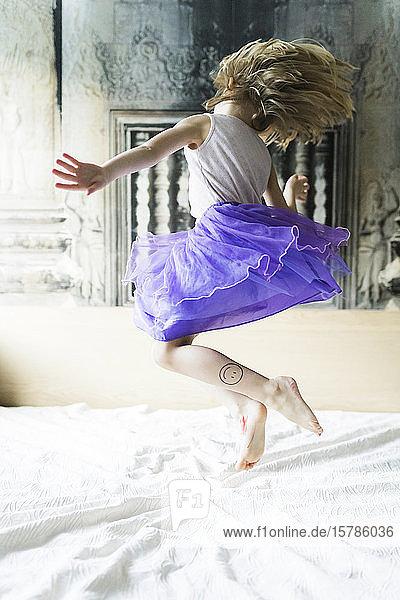 Kleines Mädchen springt auf Bett