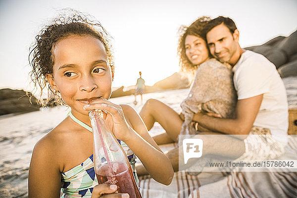 Mädchen mit ihrer Familie bei Sonnenuntergang am Strand bei einem Erfrischungsgetränk