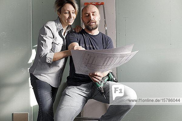 Ehepaar auf der Baustelle zu Hause studiert Plan