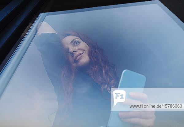 Porträt einer lächelnden rothaarigen Frau  die ihr Handy hinter einer Fensterscheibe hält