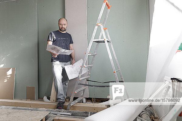 Mann auf der Baustelle zu Hause studiert Plan