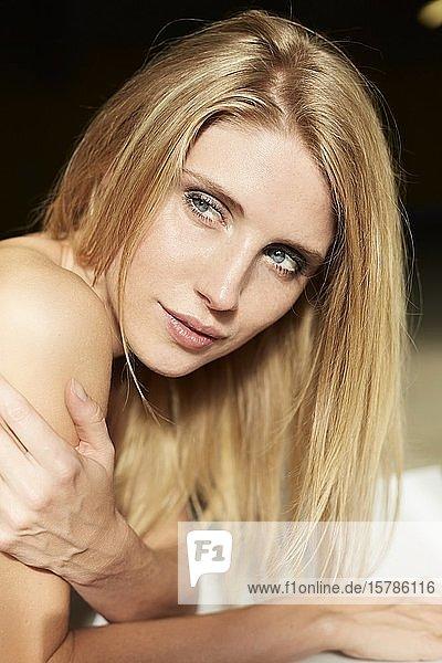 Porträt einer sexy blonden jungen Frau im Liegen