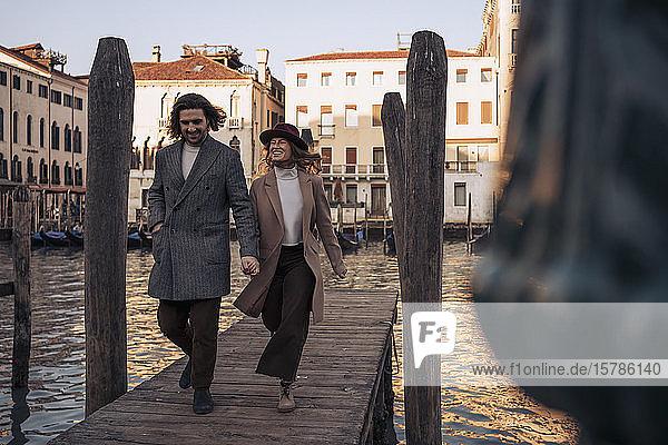 Junges Paar beim Spaziergang auf einem Steg am Canal Grande in Venedig  Italien