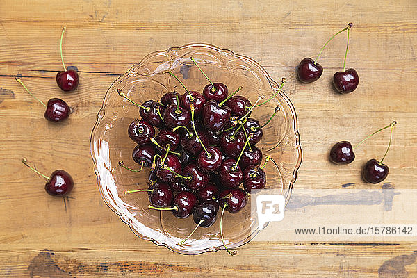 Cherries in glass bowl on wooden table