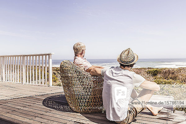 Father and adult son sitting on a terrace at the sea