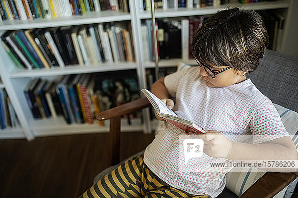 Boy with glasses sitting on armchair reading book