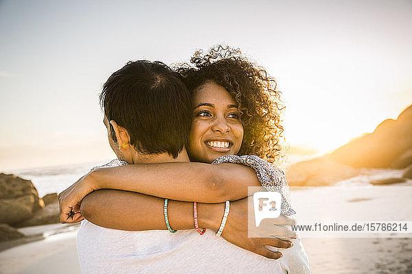 Glückliches Paar umarmt sich bei Sonnenuntergang am Strand