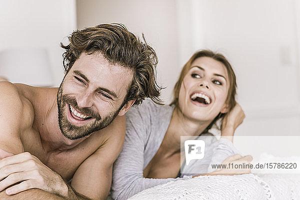 Lachendes junges Paar liegt im Bett