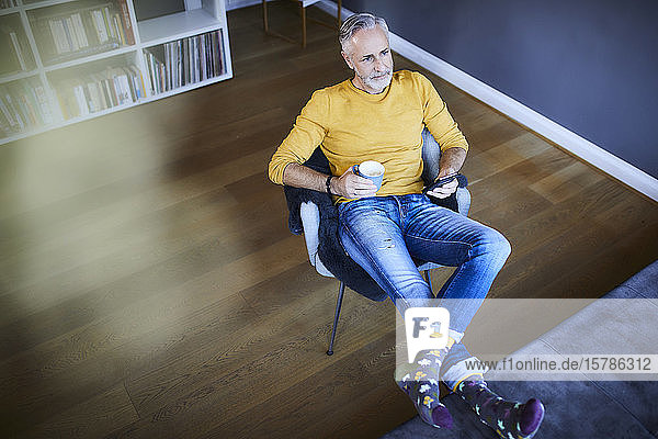 Relaxed mature man at home with cell phone and cup of coffee