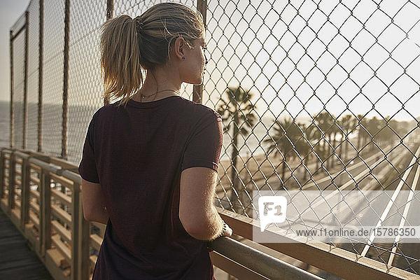 Sportliche junge Frau steht auf einer Brücke und schaut durch einen Zaun