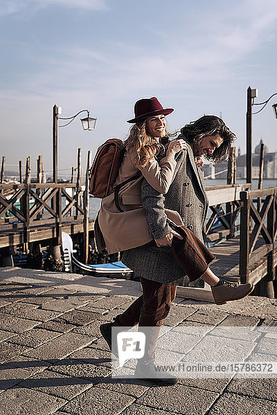Junger Mann nimmt seine Freundin am Hafen von Venedig  Italien  huckepack