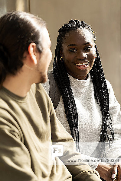 Portrait of young woman smiling at man outdoors