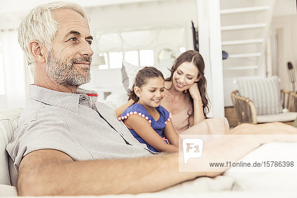 Smiling mature man with family on couch in living room