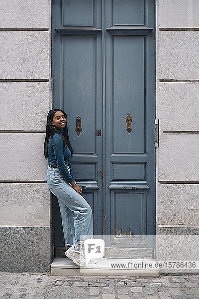 Porträt einer lächelnden jungen Frau  die an einer Tür in der Stadt steht