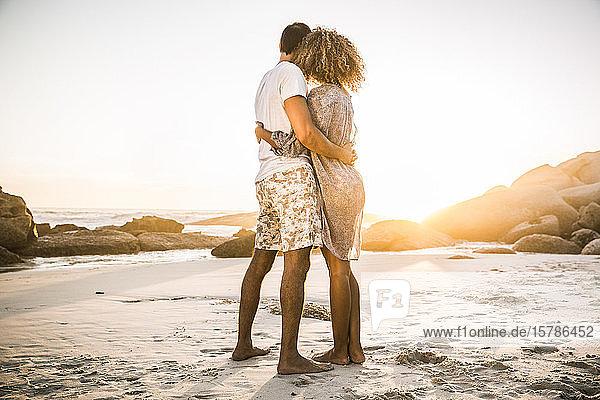 Paare umarmen sich am Strand und genießen den Sonnenuntergang