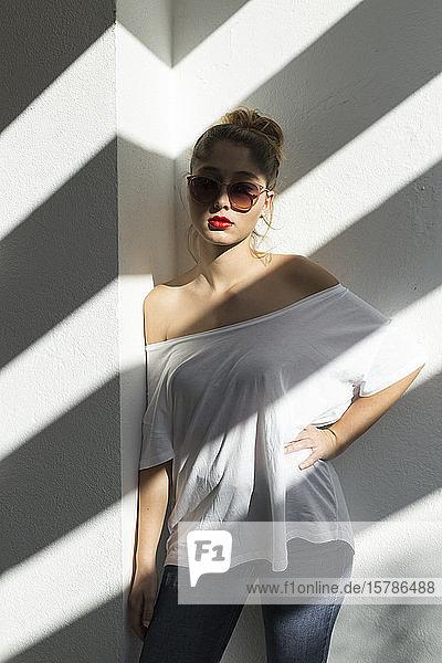 Bildnis einer jungen Frau mit roten Lippen und Sonnenbrille