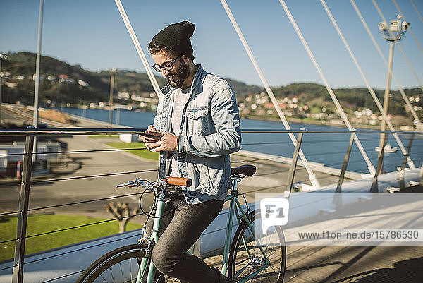 Young man commuting in the city with his fixie bike  using smartphone