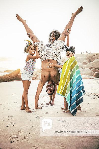 Glückliche Familie hat Spaß am Strand und hält den Vater beim Handstand
