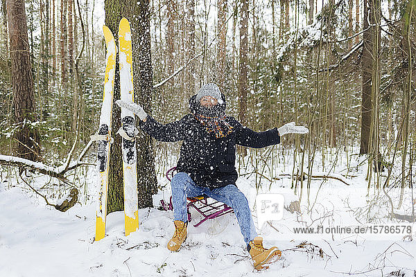 Woman with skis sitting on sledge in winter forest throwing snow into the air