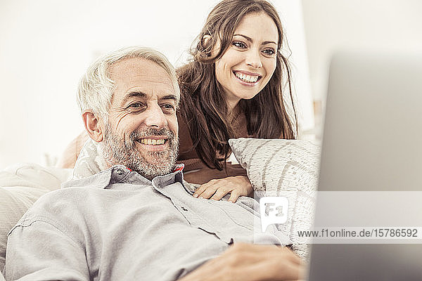 Smiling mature man using laptop on couch at home with woman watching