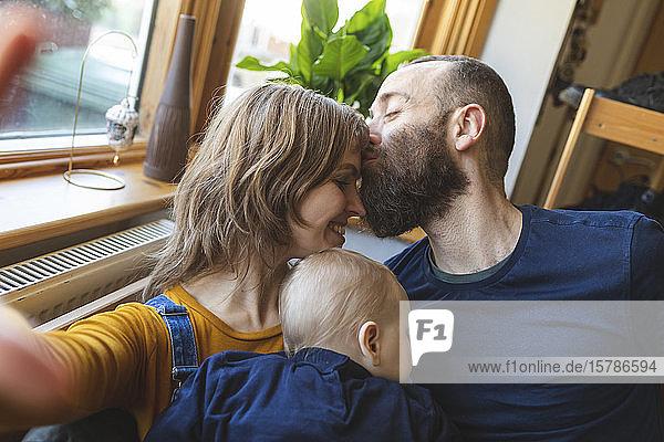 Selbstsüchtige  liebevolle Familie auf dem Sofa mit schlafendem kleinen Sohn