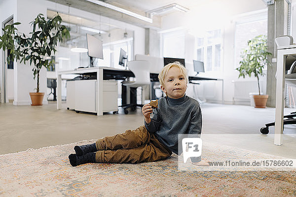 Boy sitting on carpet in office eating bread