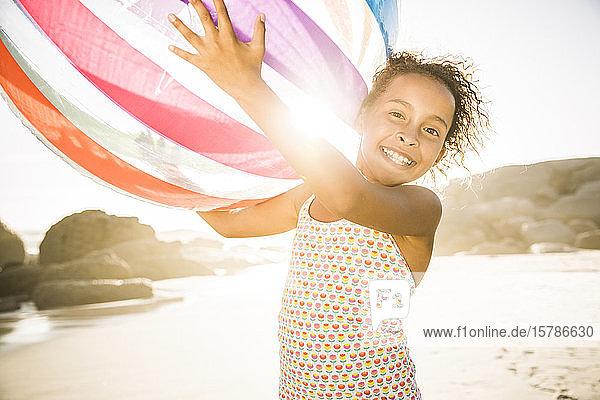 Glückliches Mädchen hält aufblasbaren Ball am Strand