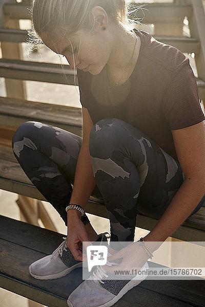 Junge Frau schnürt ihre Schuhe vor dem Laufen