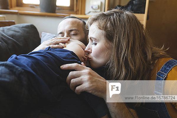 Liebende Familie auf dem Sofa mit schlafendem kleinen Sohn