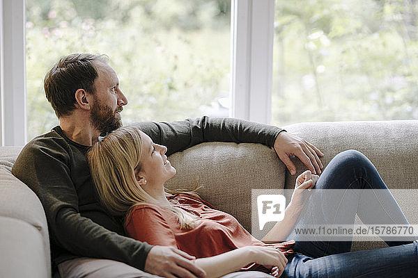 Paar sitzt zu Hause auf der Couch und entspannt