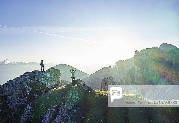 Wanderer  die auf einem Felsvorsprung stehen und auf die Berge blicken
