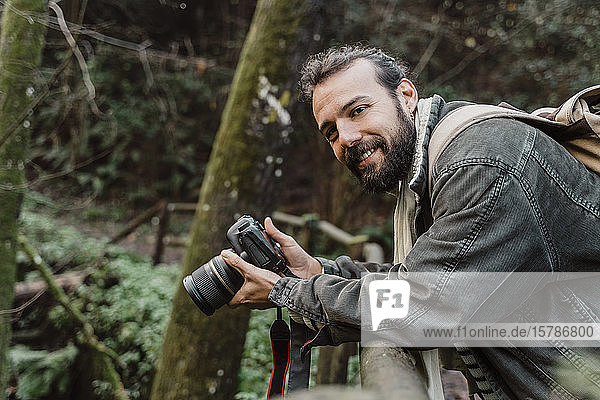Young man taking pictures in the forest with his camera