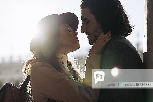 Zärtliches junges Paar küsst sich im Gegenlicht