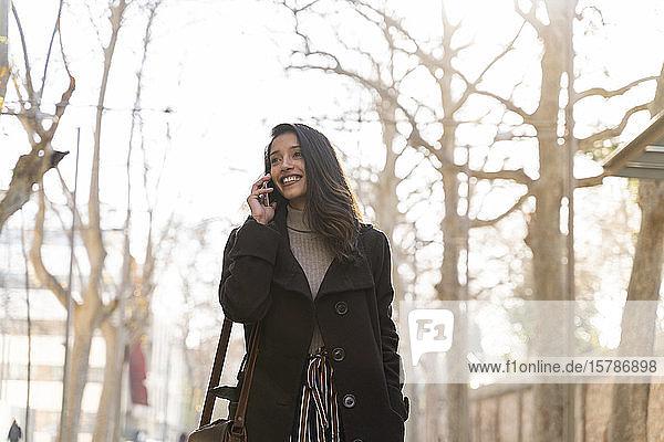 Lächelnde junge Frau am Telefon in der Stadt