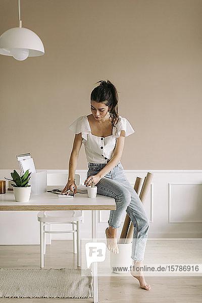 Junge Frau sitzt zu Hause am Tisch