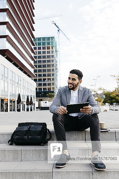 Casual young businessman sitting on stairs in the city using tablet