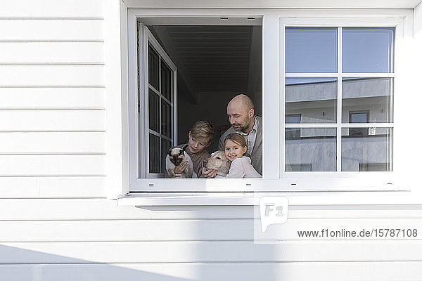 Vater mit seinen zwei Kindern  Hund und Katze am geöffneten Fenster ihres Hauses