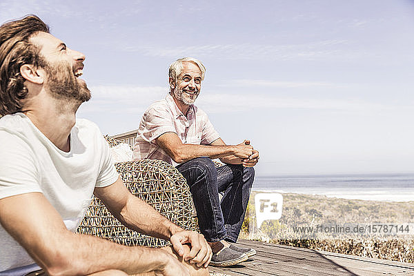 Father and adult son hanging out and having fun together on a terrace at the sea