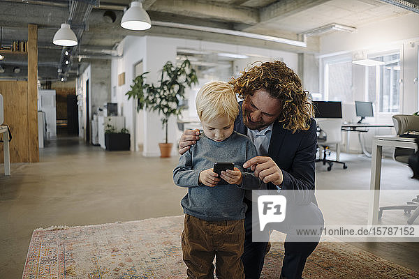 Businessman with son in office using cell phone
