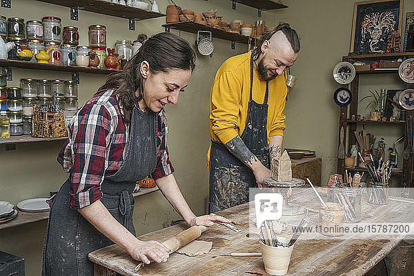 Two potters working together in workshop