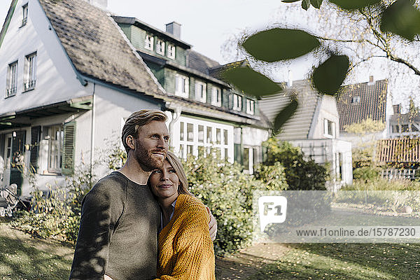 Lächelndes Paar umarmt sich im Garten ihres Hauses