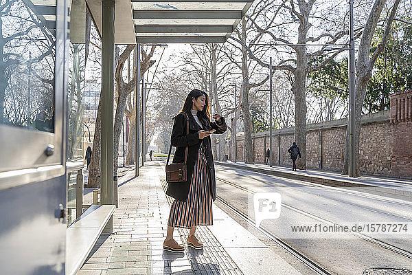 Junge Frau wartet an der Straßenbahnhaltestelle
